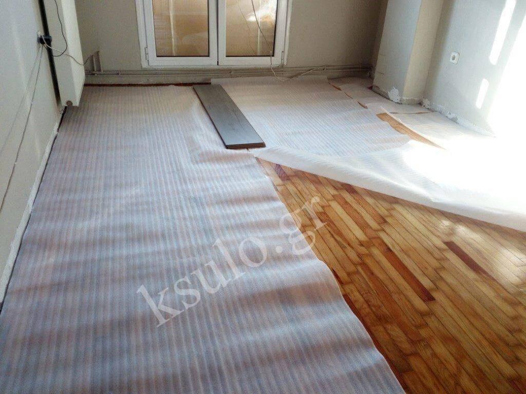 Ξύλινο δάπεδο σε σαλόνι το μισό είναι επικαλυμμένο με προστατευτικό πανί.